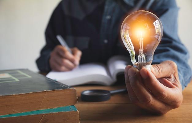 Mano del maschio che tiene una lampadina con una pila di libri