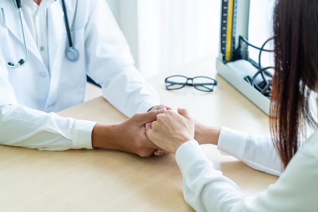Mano del medico che rassicura la sua paziente