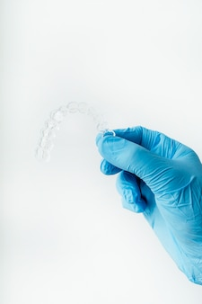 Mano del medico che tiene un chiaro allineatore dentale