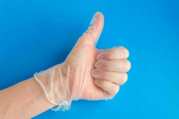 Mano del medico in guanto di lattice medica dando pollice in alto segno. come sullo sfondo blu