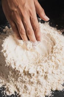 Mano del panettiere del primo piano che prepara farina