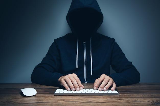 Mano del pirata informatico in guanto che lavora al computer portatile