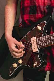 Mano del primo piano che gioca bella chitarra