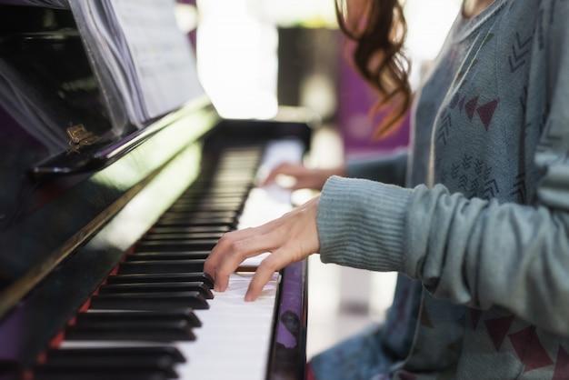 Mano del primo piano che gioca sul piano classico