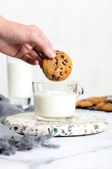 Mano del primo piano che immerge biscotto di cioccolato in latte