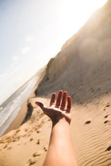 Mano del primo piano che indica al paesaggio della spiaggia