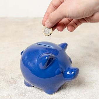 Mano del primo piano che mette una moneta in un porcellino salvadanaio