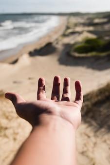 Mano del primo piano che raggiunge al paesaggio della spiaggia