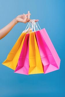 Mano del primo piano che tiene i sacchetti della spesa rosa e gialli variopinti isolati sopra il blu