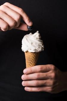 Mano del primo piano che tiene il gelato saporito con la bacca