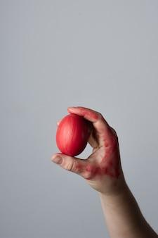 Mano del primo piano che tiene l'uovo di pasqua tradizionale