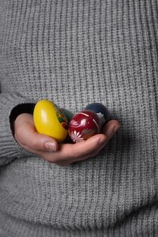 Mano del primo piano che tiene le uova di pasqua dipinte a mano