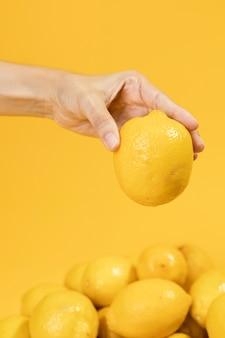 Mano del primo piano che tiene limone crudo
