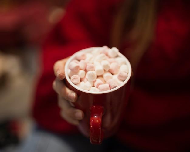 Mano del primo piano che tiene tazza con marshmallow