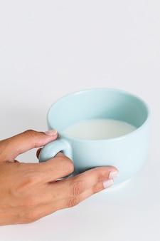 Mano del primo piano che tiene tazza di ceramica con latte
