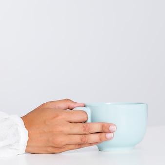Mano del primo piano che tiene tazza di ceramica