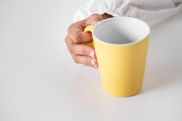 Mano del primo piano che tiene tazza gialla