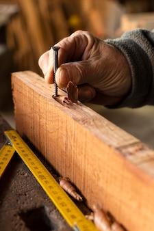 Mano del primo piano che tiene un chiodo in legno