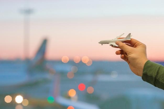 Mano del primo piano che tiene un giocattolo del modello dell'aeroplano alla grande finestra del fondo dell'aeroporto