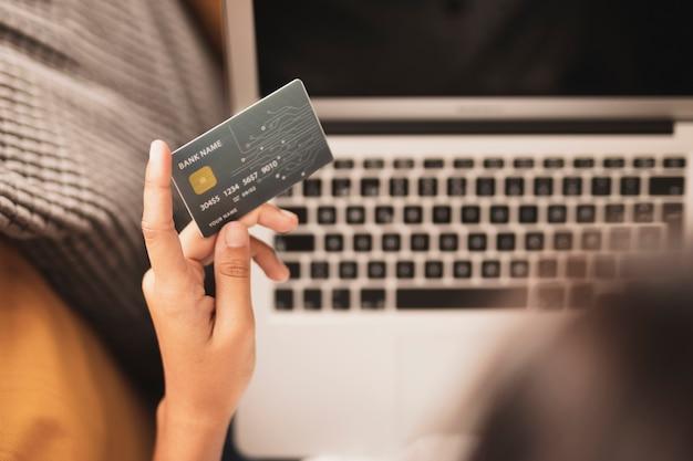 Mano del primo piano che tiene una carta di credito