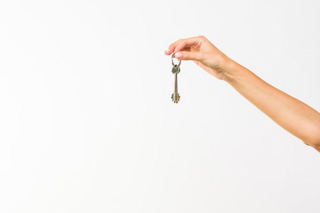 Mano del primo piano che tiene una chiave con copia-spazio