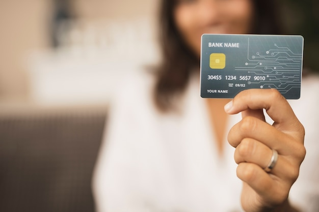 Mano del primo piano che tiene una derisione della carta di credito