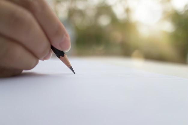 Mano del primo piano che tiene una matita nera, scrittura femminile della mano con una matita su un libro bianco di mattina con luce solare di mattina.