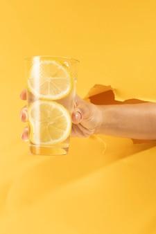 Mano del primo piano che tiene vetro di limonata