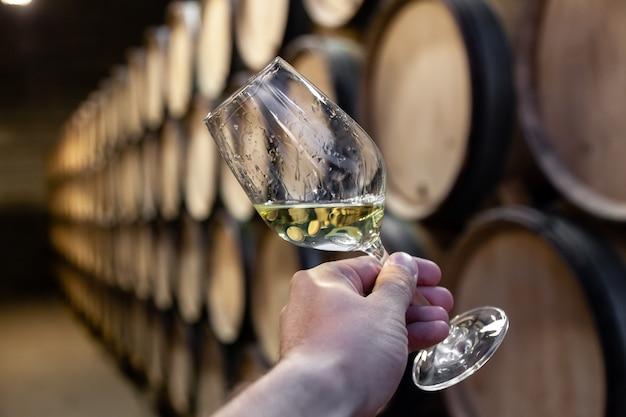 Mano del primo piano con bicchiere di vino bianco su botti di rovere in legno di sfondo accatastati in file diritte in ordine, vecchia cantina della cantina, volta.