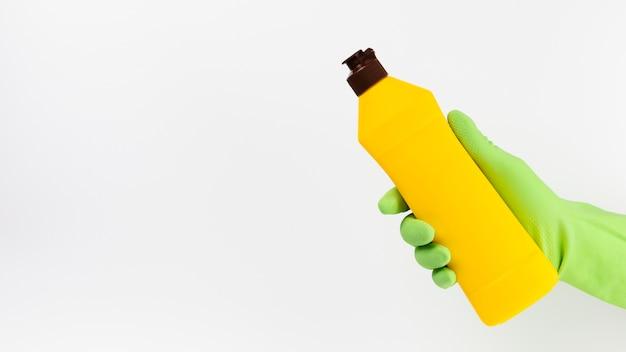 Mano del primo piano con il guanto verde che sostiene detersivo