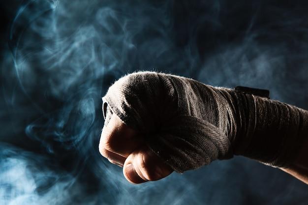 Mano del primo piano con la fasciatura del kickboxing di addestramento dell'uomo muscolare su fumo nero e blu