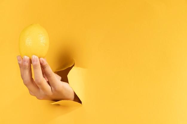 Mano del primo piano con lo spazio della copia e del limone