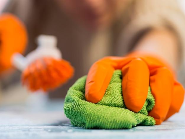 Mano del primo piano con pulizia dei guanti di gomma