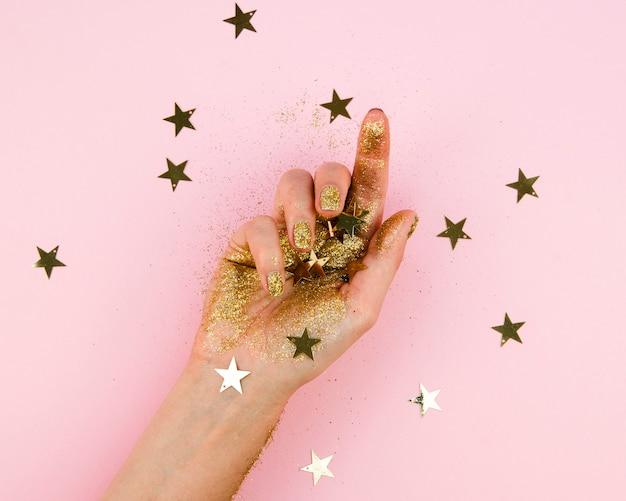 Mano del primo piano con stelle dorate