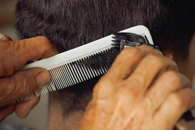 Mano del primo piano dei capelli di taglio del parrucchiere con il tagliatore al negozio di barbiere locale.