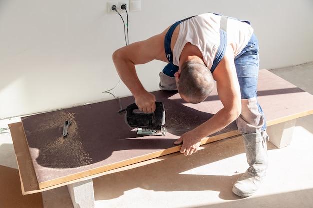 Mano del primo piano del carpentiere, falegname con fretsaw o seghetto da taglio professionale, taglio da tavolo in legno, tavola da taglio, limatura marrone, segatura. laboratorio di falegnameria, lavoro manuale