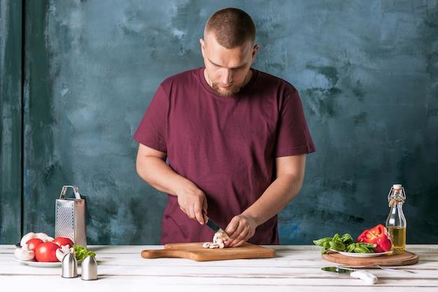 Mano del primo piano del panettiere del cuoco unico che produce pizza alla cucina