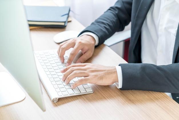 Mano del primo piano dell'uomo d'affari che per mezzo del computer