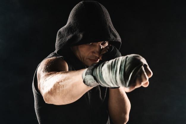 Mano del primo piano dell'uomo muscolare con la fasciatura