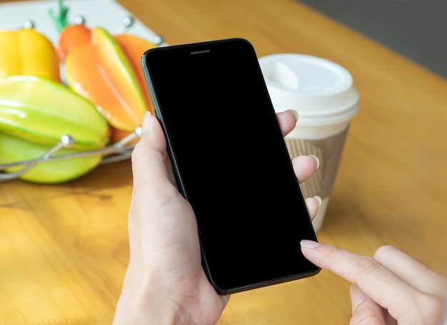 Mano del primo piano della donna nella casa facendo uso dello smartphone moderno per acquisto online.