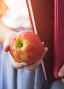 Mano del primo piano della scolara con la mela