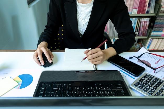 Mano del primo piano delle donne di affari con scrittura di carta al grafico, facendo uso del computer portatile del taccuino del computer.