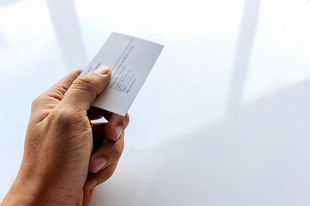 Mano del primo piano di un biglietto da visita tenere uomo con soft-focus e oltre la luce in background
