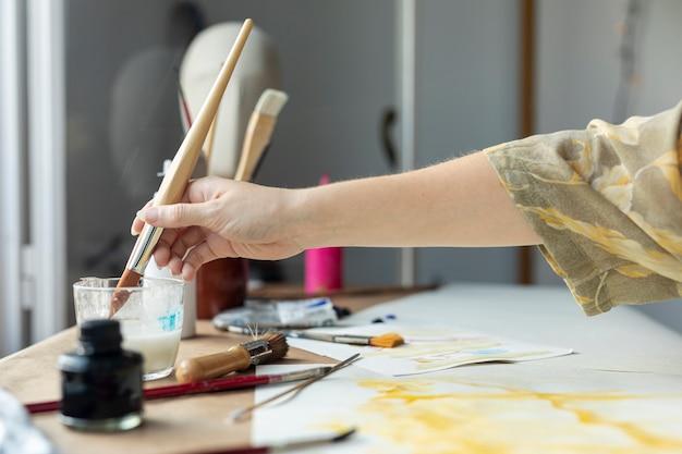 Mano del primo piano facendo uso dell'acquerello per dipingere