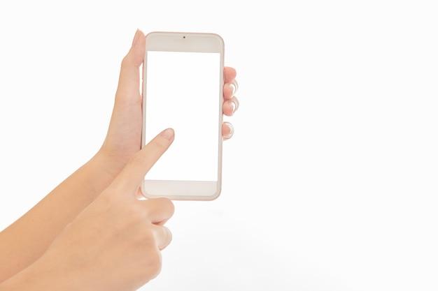 Mano del primo piano utilizzando lo schermo bianco vuoto mobile del telefono isolato su bianco.