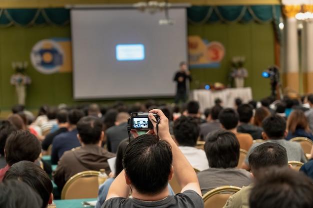 Mano del pubblico dell'uomo del primo piano che tiene la macchina fotografica astuta per la presa della foto o fare streaming in tensione