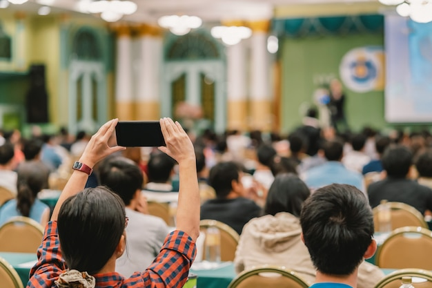 Mano del pubblico della donna del primo piano che tiene telefono astuto per la presa della foto o fare streghetta in tensione