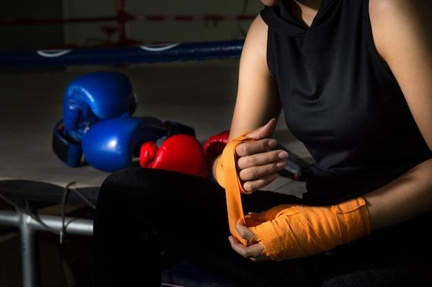 Mano del pugile della donna del primo piano mentre indossando la cinghia arancio sul polso