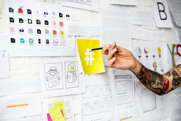 Mano del tatuaggio che indica sul segno di hashtag sulla parete gialla della nota a bordo