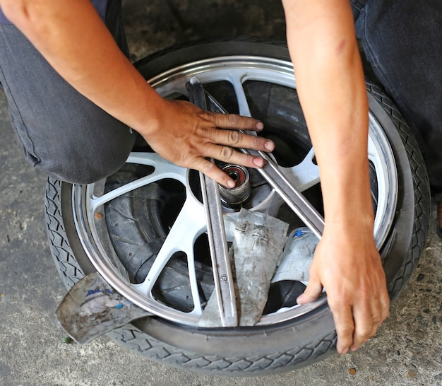 Mano del tecnico che ripara la ruota del motociclo